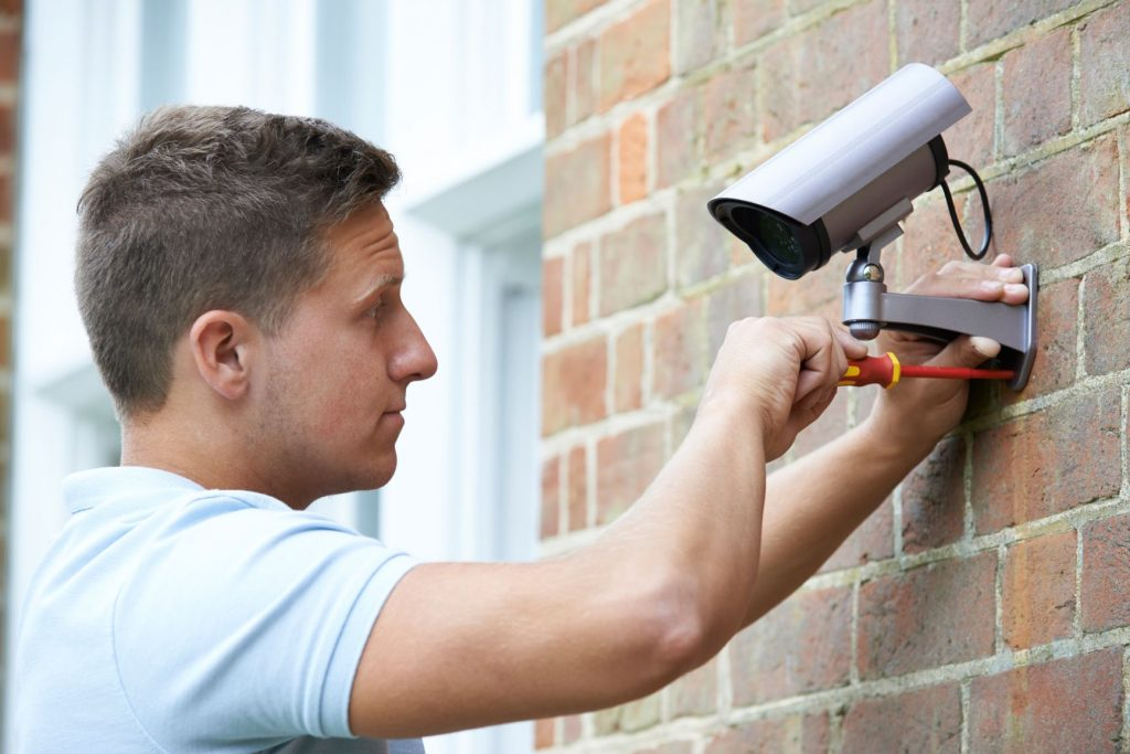 Picture of somebody putting up a CCTV camera on a wall